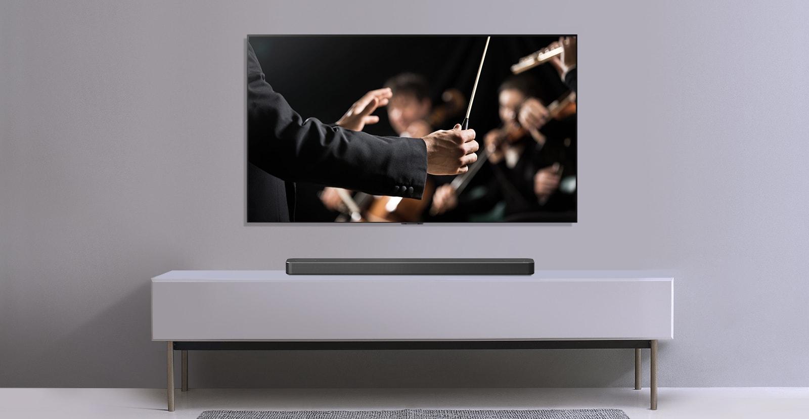 Na sivi steni je televizor, pod njim na sivi polici pa je zvočnik LG Sound Bar. Televizija prikazuje dirigenta, ki dirigira orkestru.