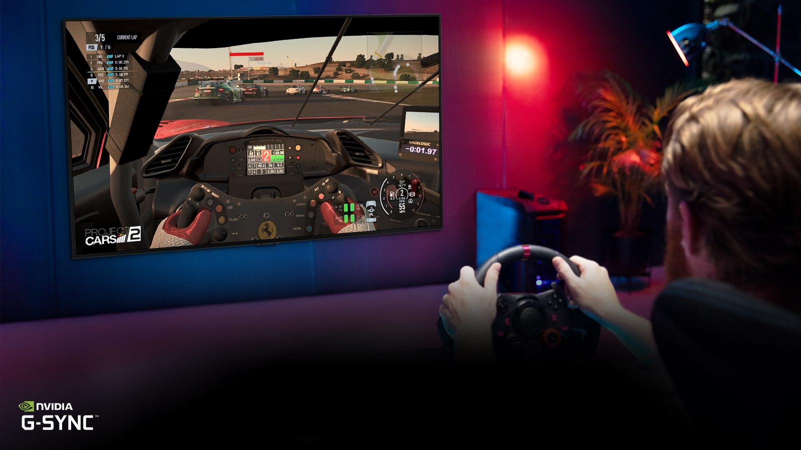 Moški, ki sedi na stolu, namenjenem igranju dirkalnih video iger, drži dirkalno kolo, medtem ko na televizijskem zaslonu igra dirkaško video igro.