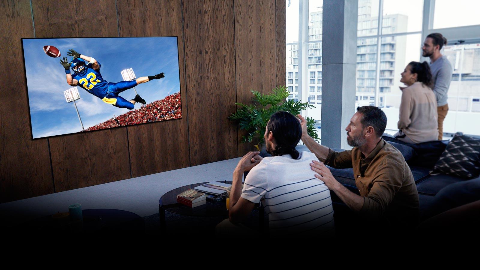 Ljudi koji gledaju utakmicu američkog nogometa na TV-u u dnevnoj sobi