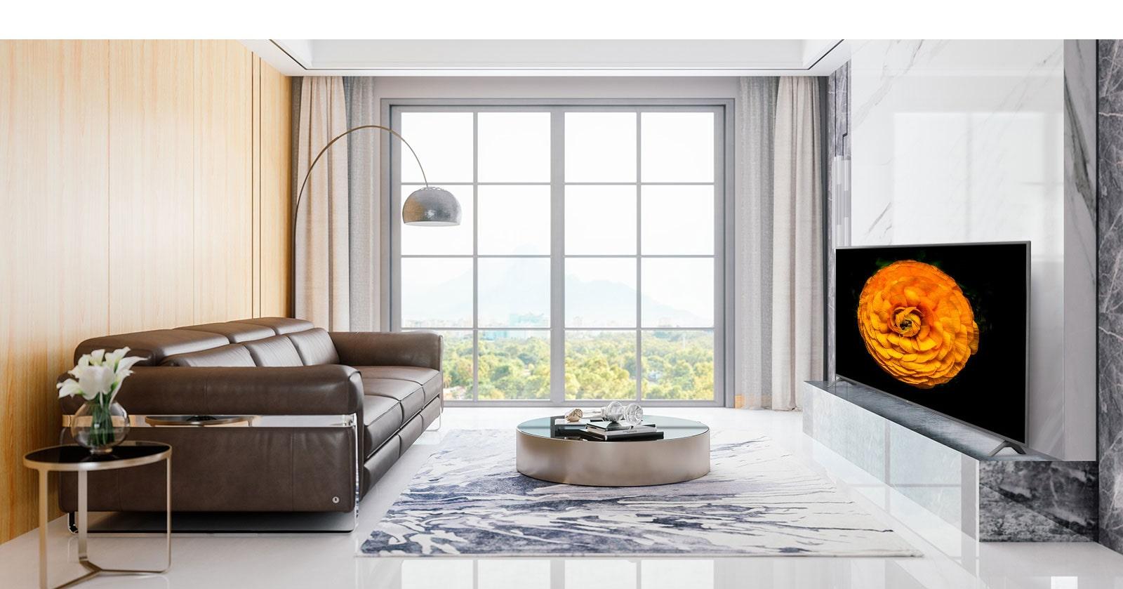 LG UHD TV na steni v dnevni sobi z minimalistično notranjostjo. Na TV zaslonu se prikaže slika rože.