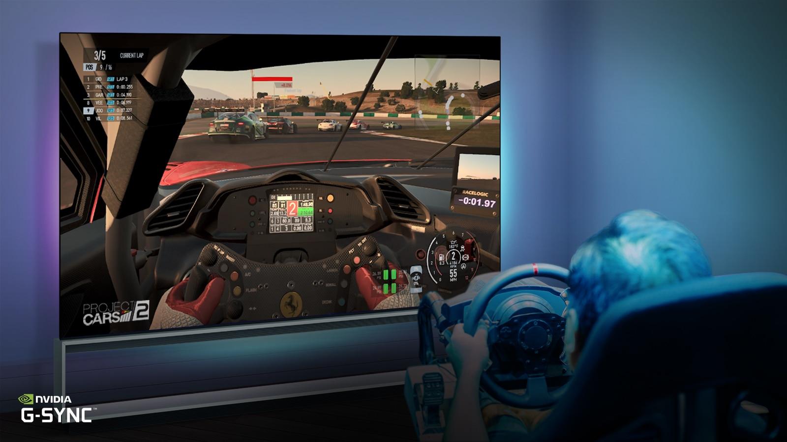 Moški, ki sedi na stolu, namenjenem igranju dirkalnih video iger, med dirkalno video igrico na TV zaslonu drži dirkaški volan