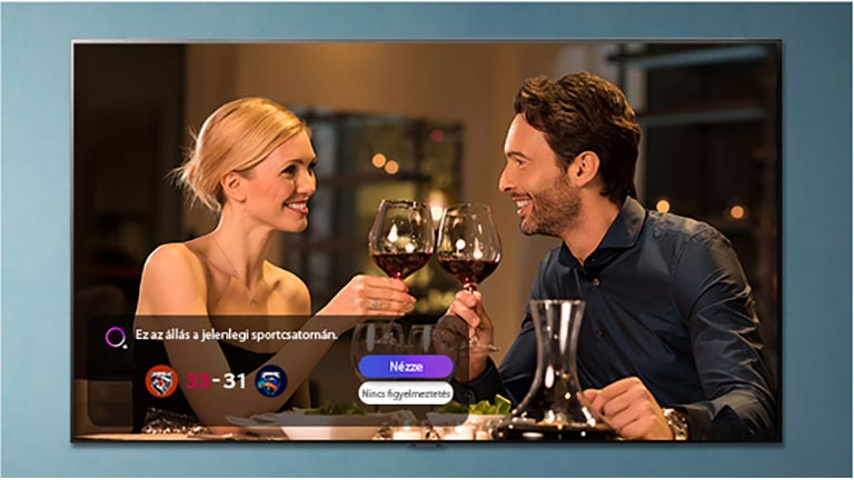 Egy férfi és egy nő koccint a TV képernyőjén, miközben megjelenik a sportfigyelmeztetés értesítése