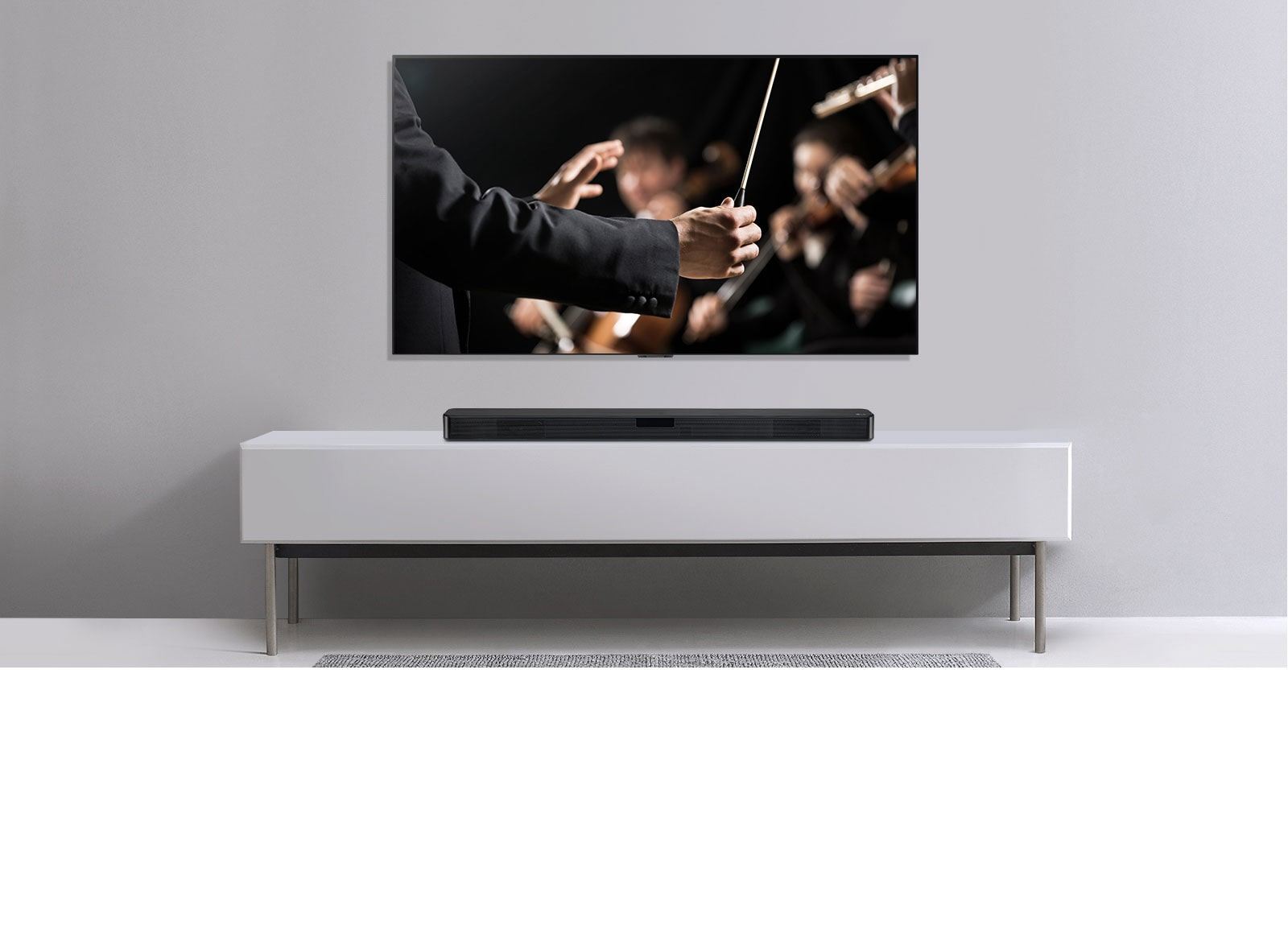 A szürke falon egy TV látható, alatta pedig egy szürke polcon az LG hangprojektor. A TV-n a karmester egy zenekart vezényel.