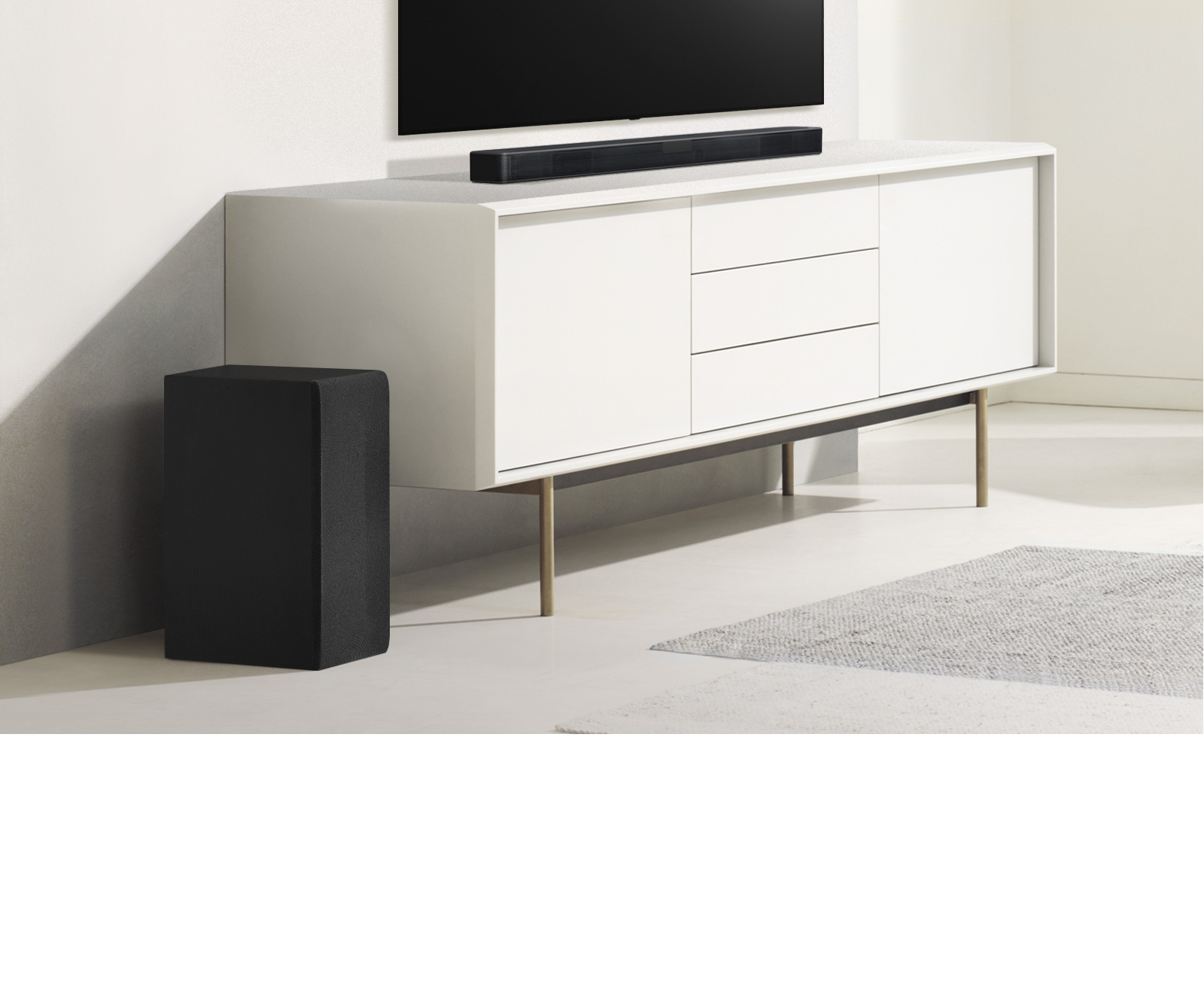 Egy fehér polcon hangprojektor látható, tőle balra pedig egy mélynyomó. A mélynyomó nagyobbnak tűnik, mivel előrébb van.