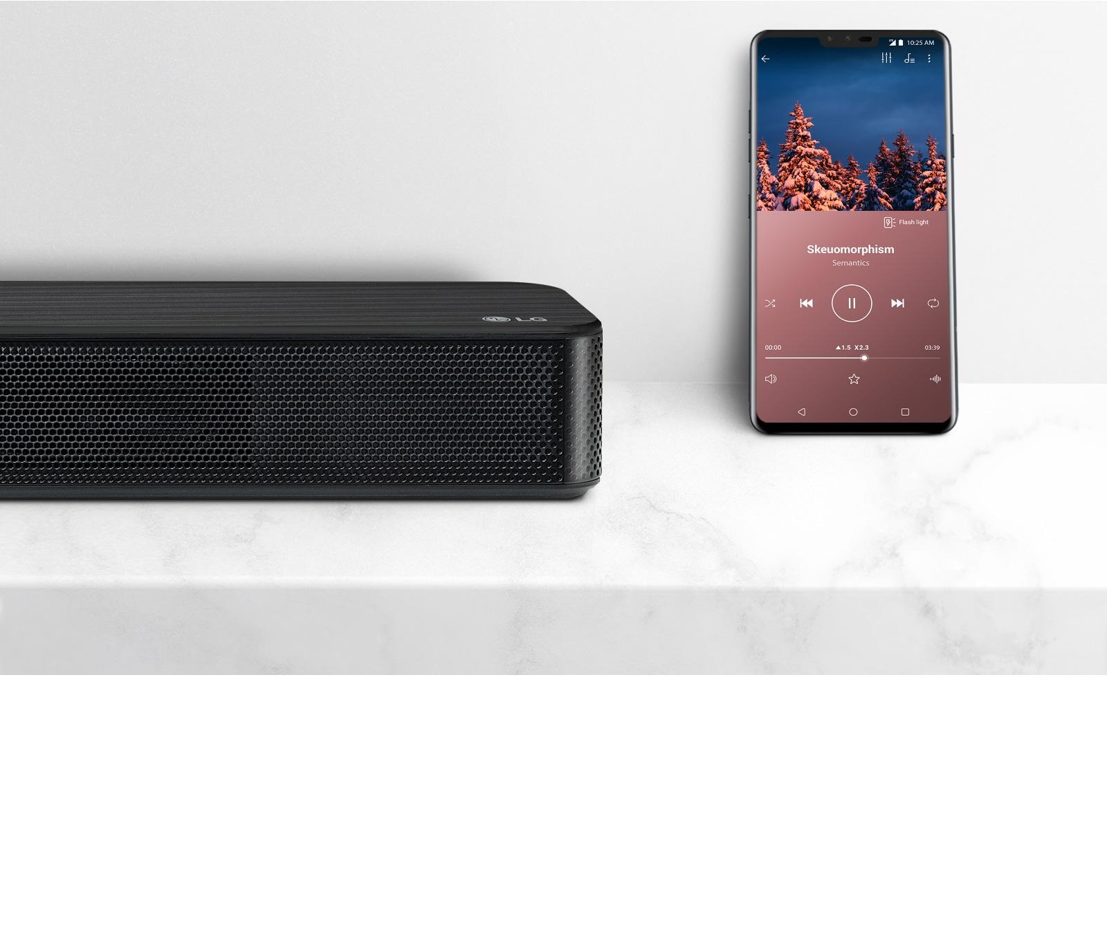 Ráközelítés az LG hangprojektor jobb oldalára, mellette egy okostelefon. Két eszköz a fehér polcon.
