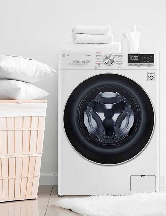 An image of LG Washing Machine with white towers and pillows around it