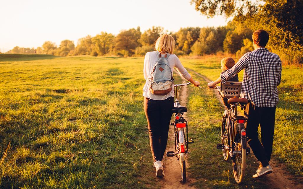 Two parents and a child in a family walking their bicycles in a paddock near the forest