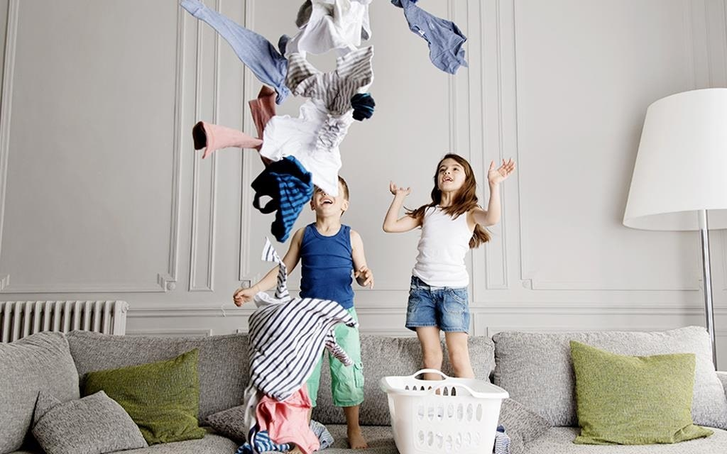 Two children throwing laundry from the basket on the sofa, in the living room with cushions and lamp in the background