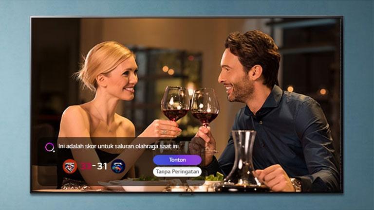 Seorang pria dan seorang wanita mendentingkan gelas di layar TV saat muncul peringatan olahraga