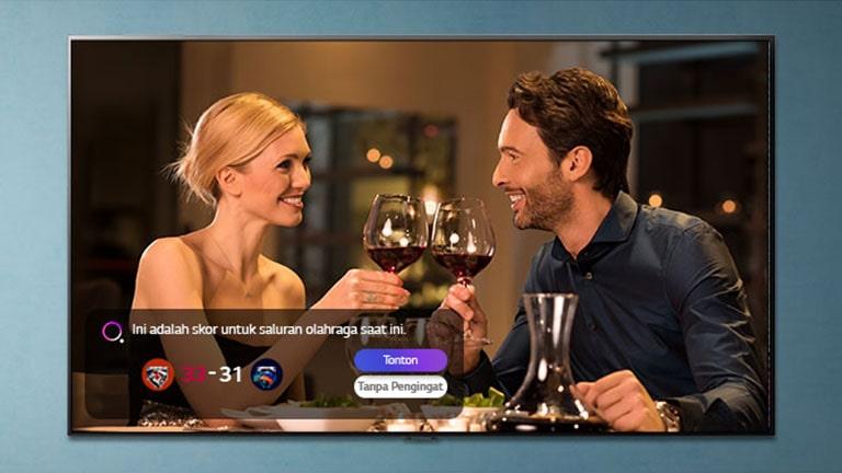 Seorang laki-laki dan perempuan mendentingkan gelas di layar TV saat muncul pengingat sports alerts