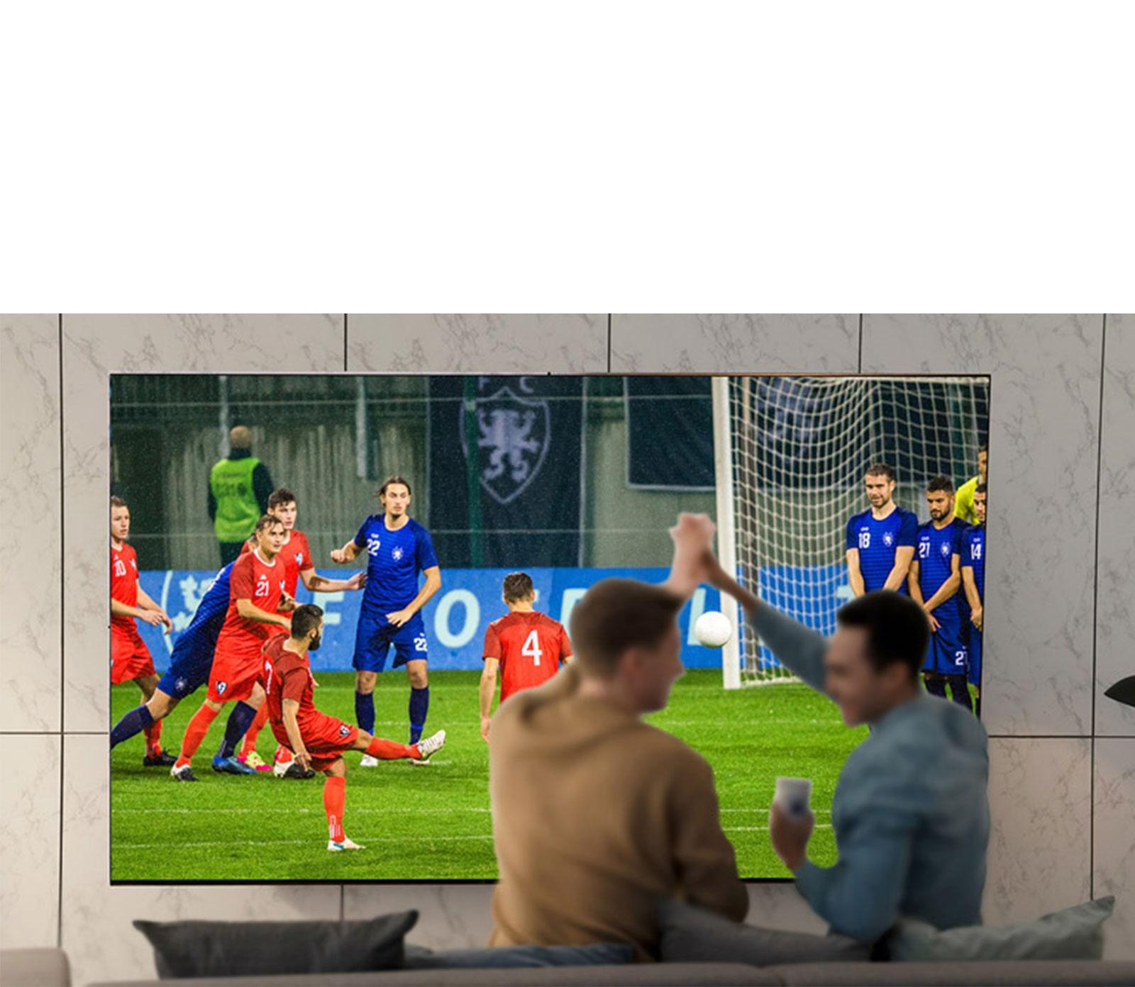 Orang menyaksikan pertandingan olahraga pada TV di sebuah ruang tamu dengan TV layar besar