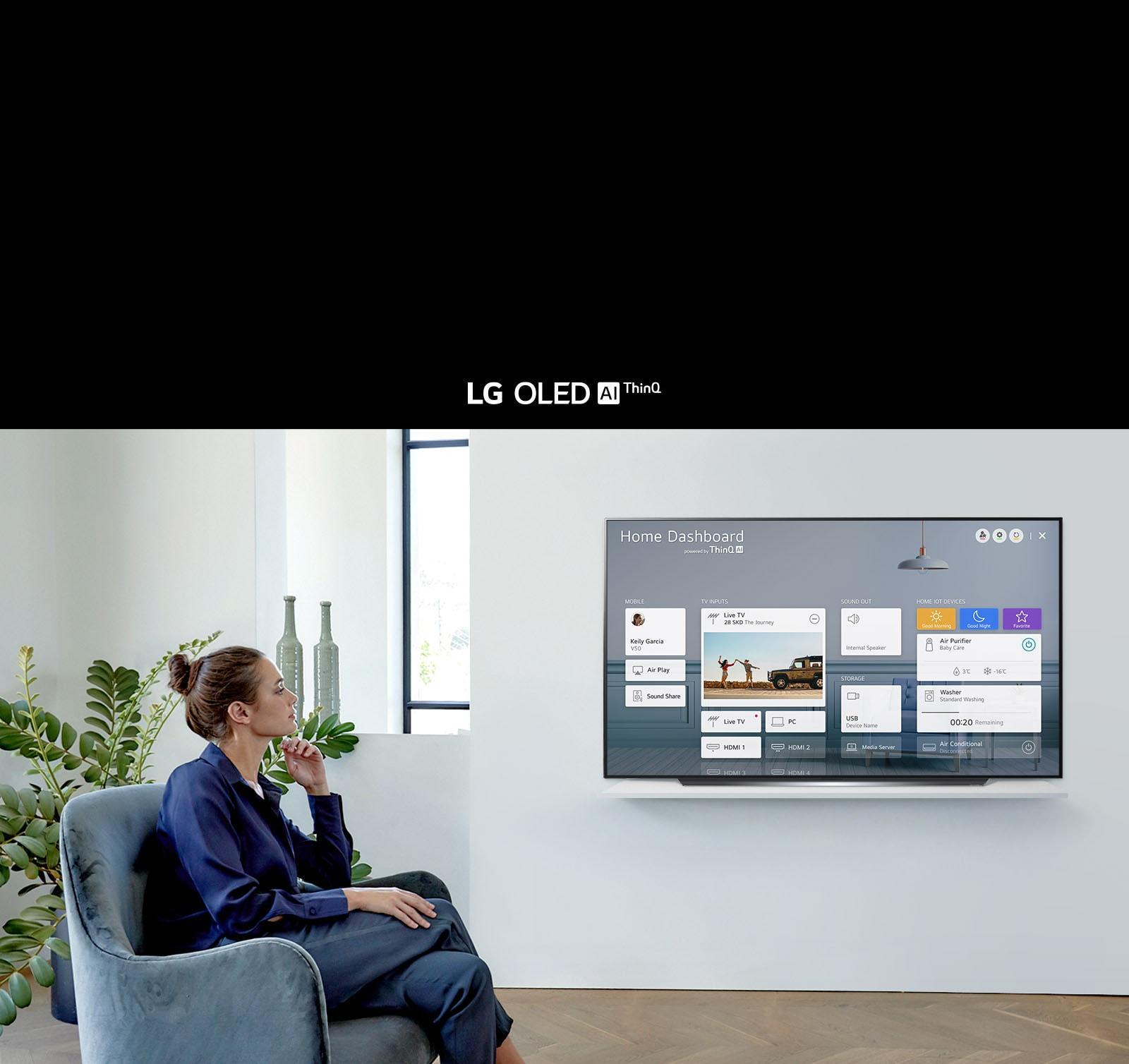 Seorang perempuan sedang duduk di kursi pada sebuah ruang keluarga dengan layar TV menampilkan Home Dashboard