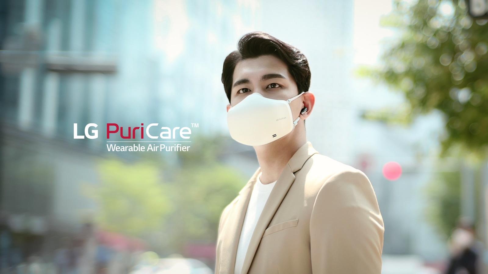 Seorang pria berdiri di tengah sebuah pusat kota dengan menggunakan LG PuriCare wearable Air Purifier yang menyala, memperhatikan sekeliling dengan latar belakang sebuah kota tampak blur