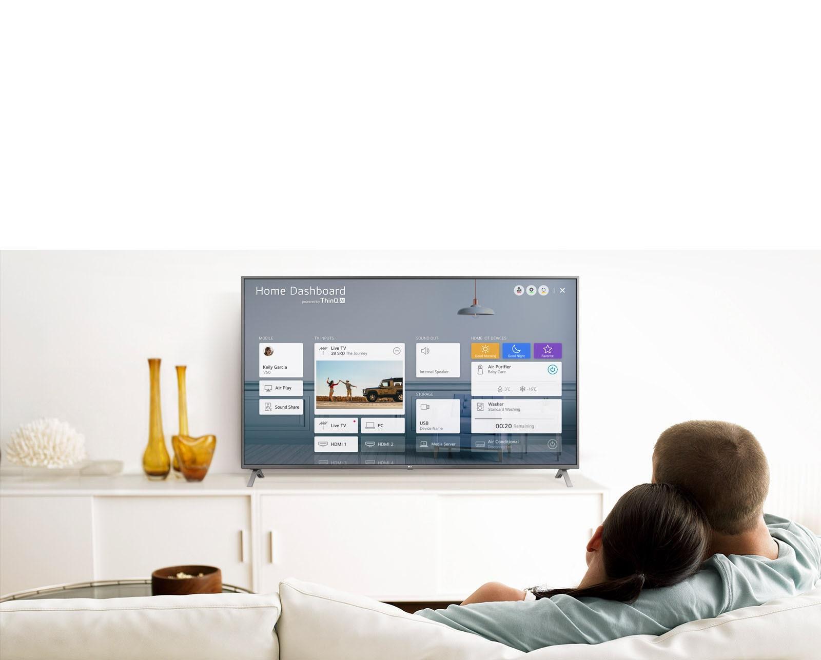 Pria dan wanita duduk di sofa pada ruang santai dengan layar TV menampilkan Home Dashboard