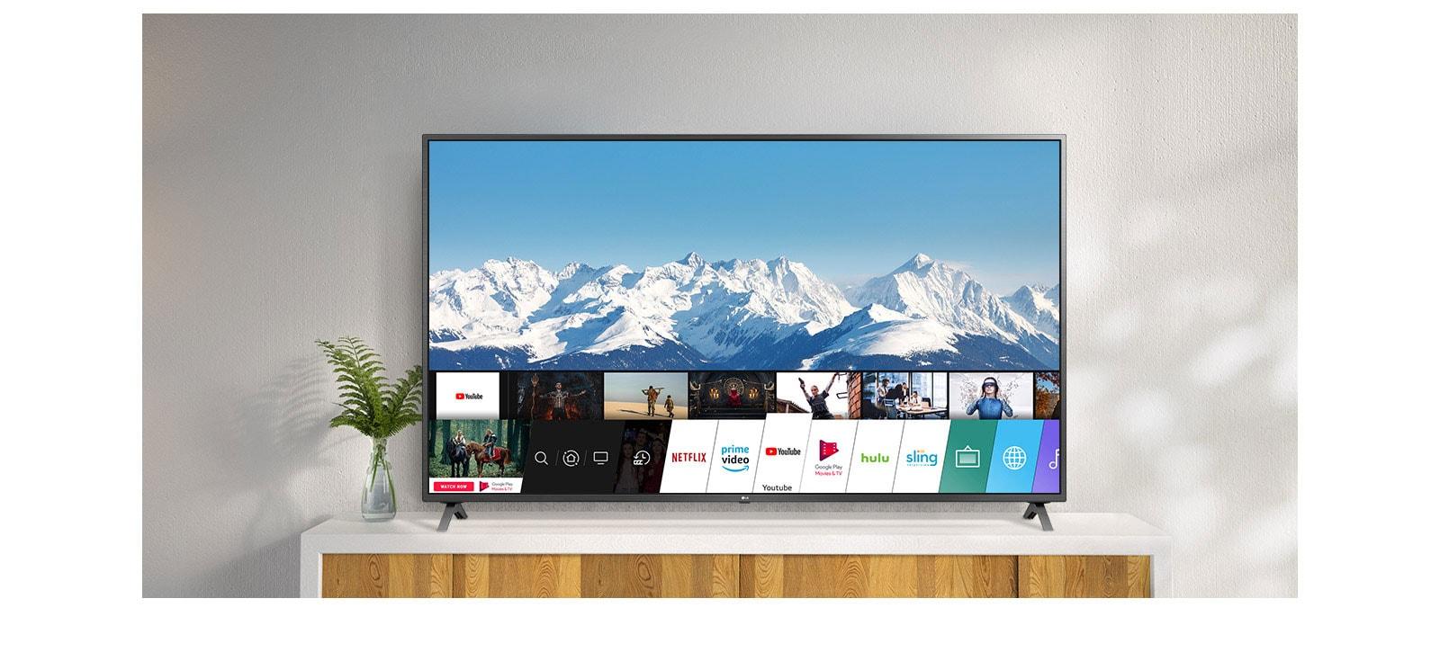 TV berdiri dengan penyangga putih di depan tembok putih. Layar TV menampilkan home screen dengan webOS.