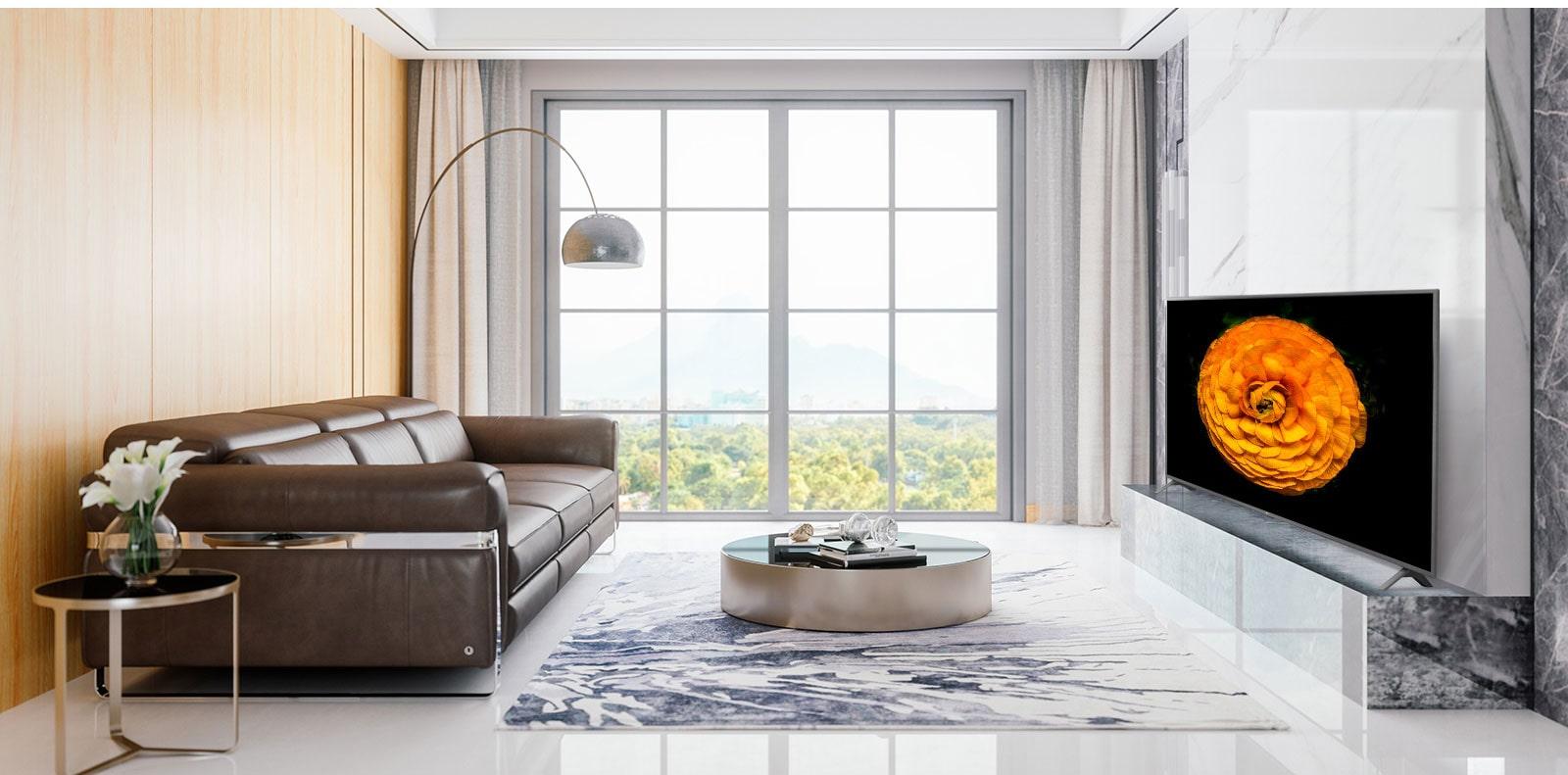 TV UHD LG, terletak pada dinding ruang santai dengan interior minimal. Layar TV menampilkan gambar bunga.