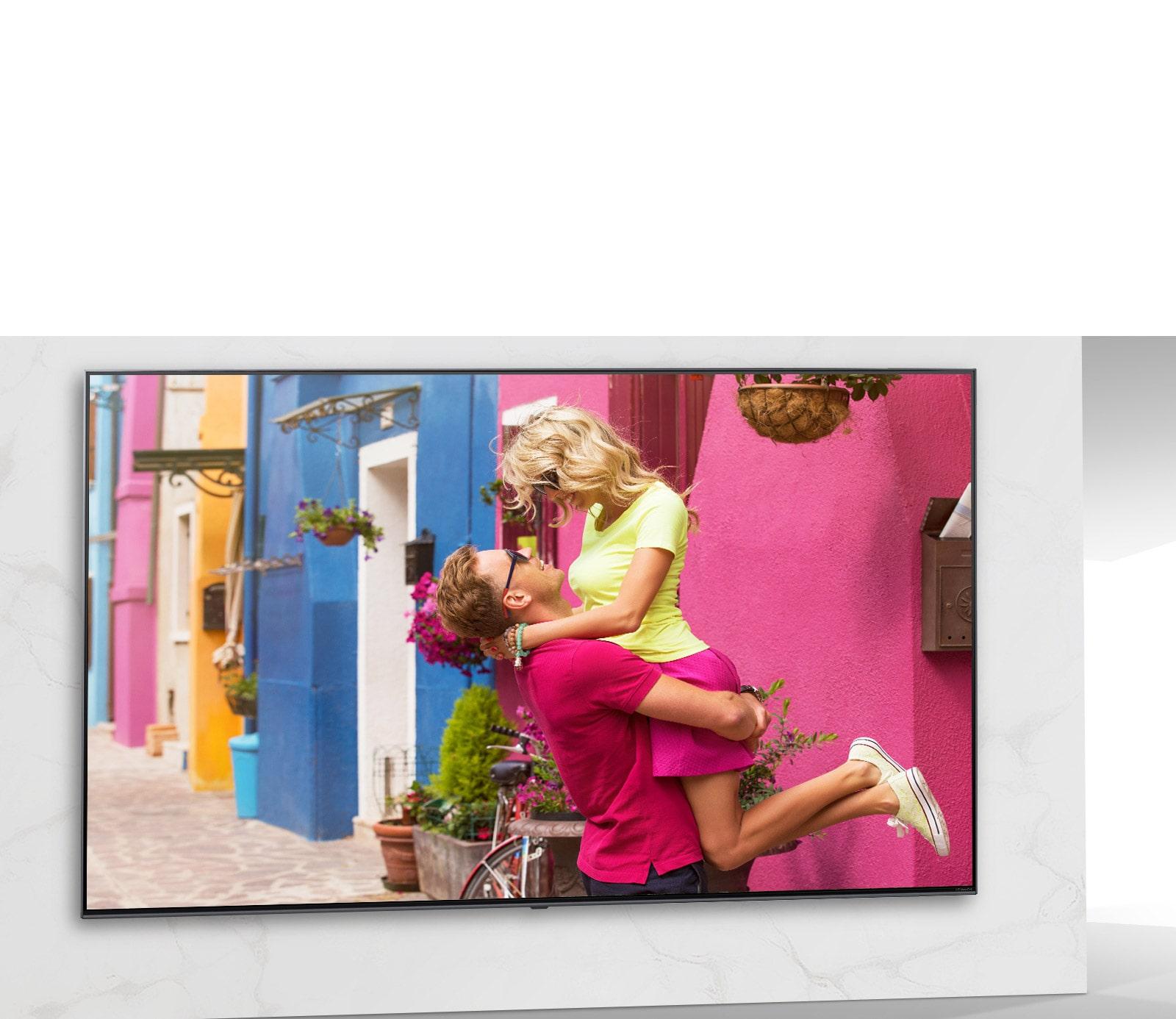 מסך טלוויזיה המציג סצנה מסרט רומנטי שבה אשה וגבר מתחבקים.