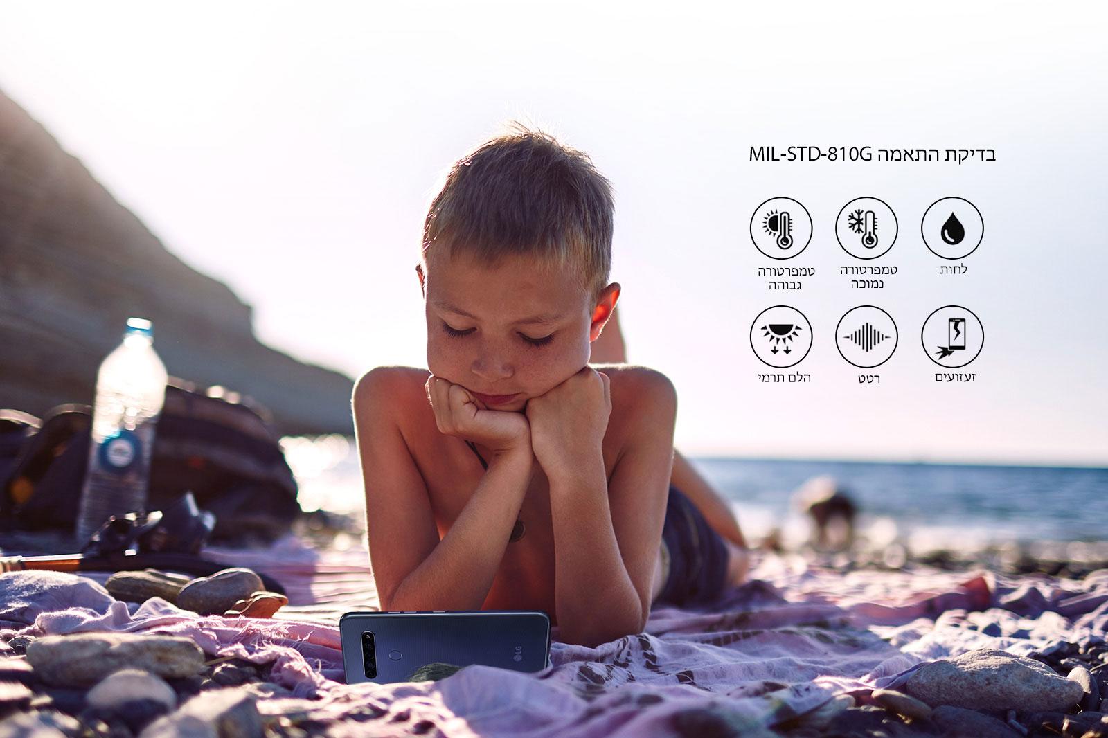 ילד שוכב בחוף הים וצופה בסרט בטלפון חכם