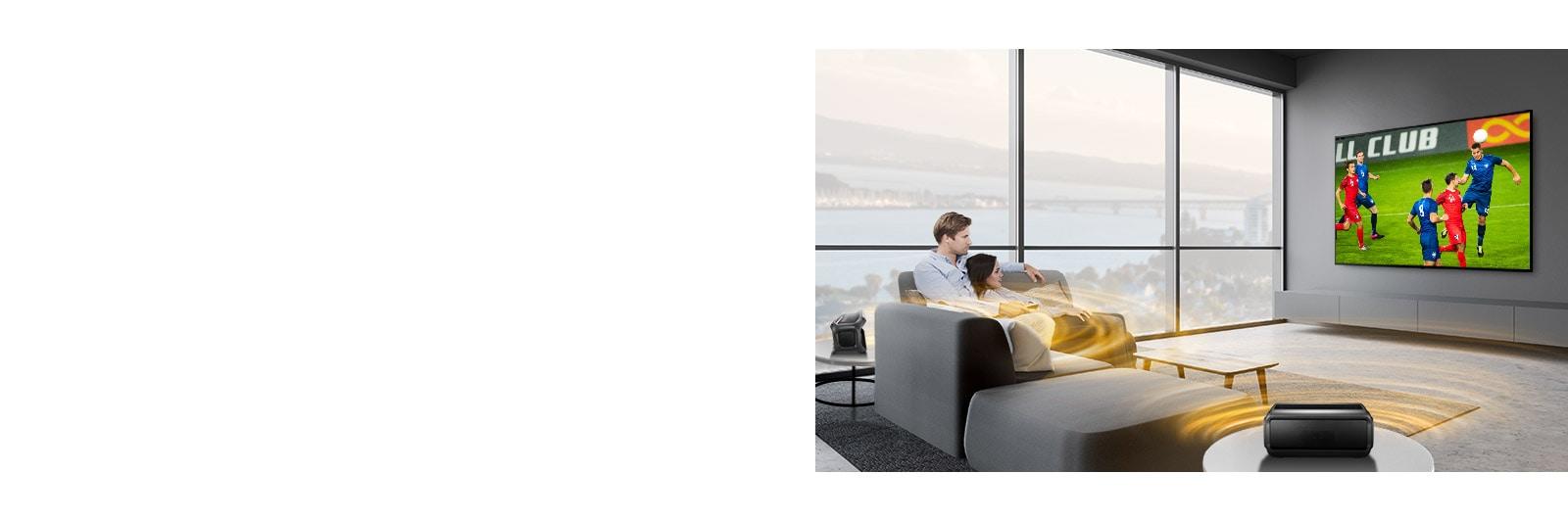Un uomo e una donna che guardano una partita su un TV in soggiorno con altoparlanti Bluetooth posteriori