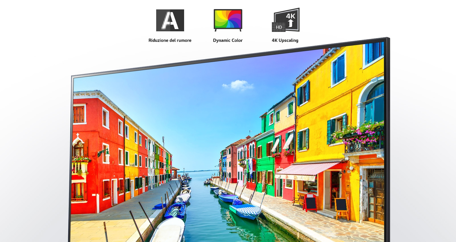 A television screen showing a harbor town with colorful houses and small boats moored on a long, narrow canal.