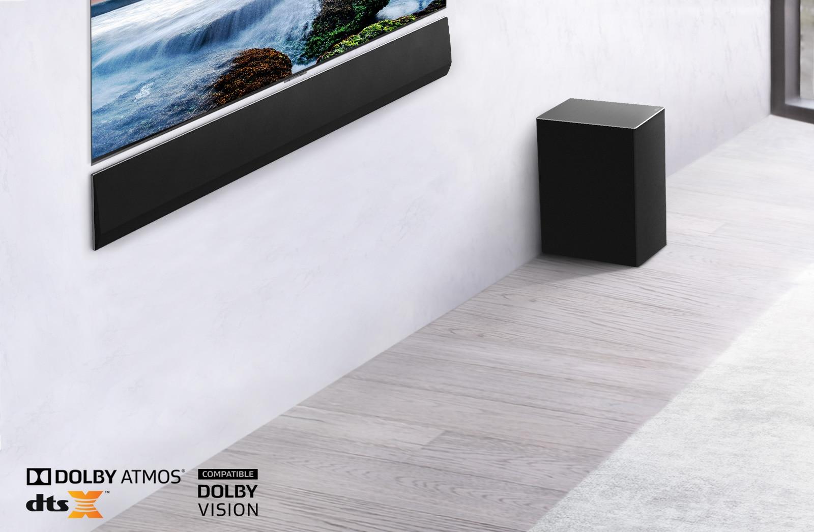 TV e LG Soundbar montati a parete con un subwoofer in basso a destra. La TV mostra un tramonto sul mare.