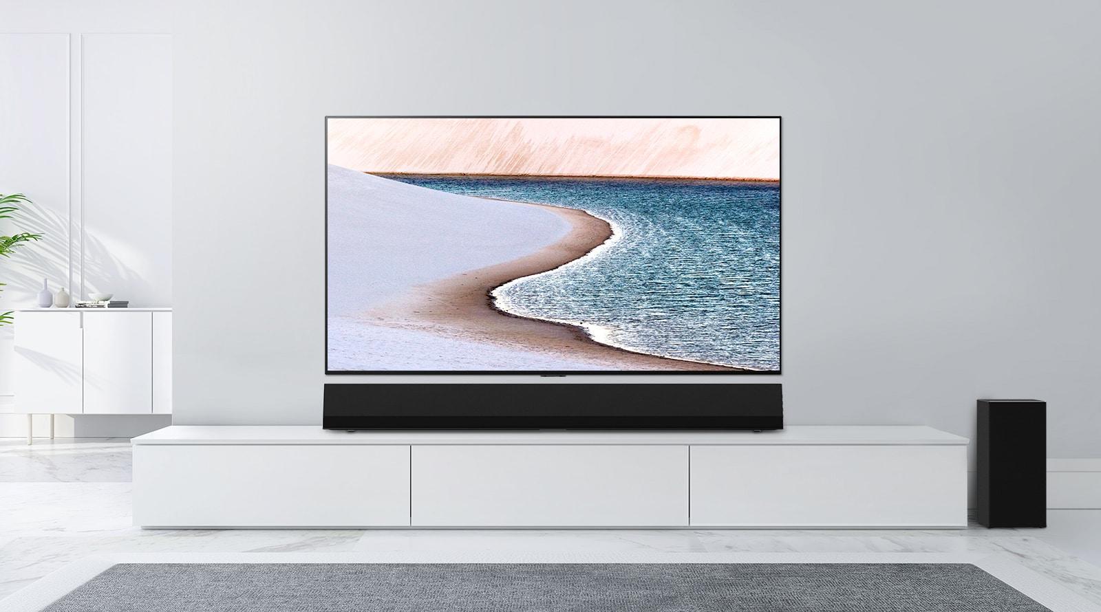 TV montata su una parete grigio chiaro. La suondbar LG è posizionata sotto su un mobile bianco. La TV mostra una spiaggia.