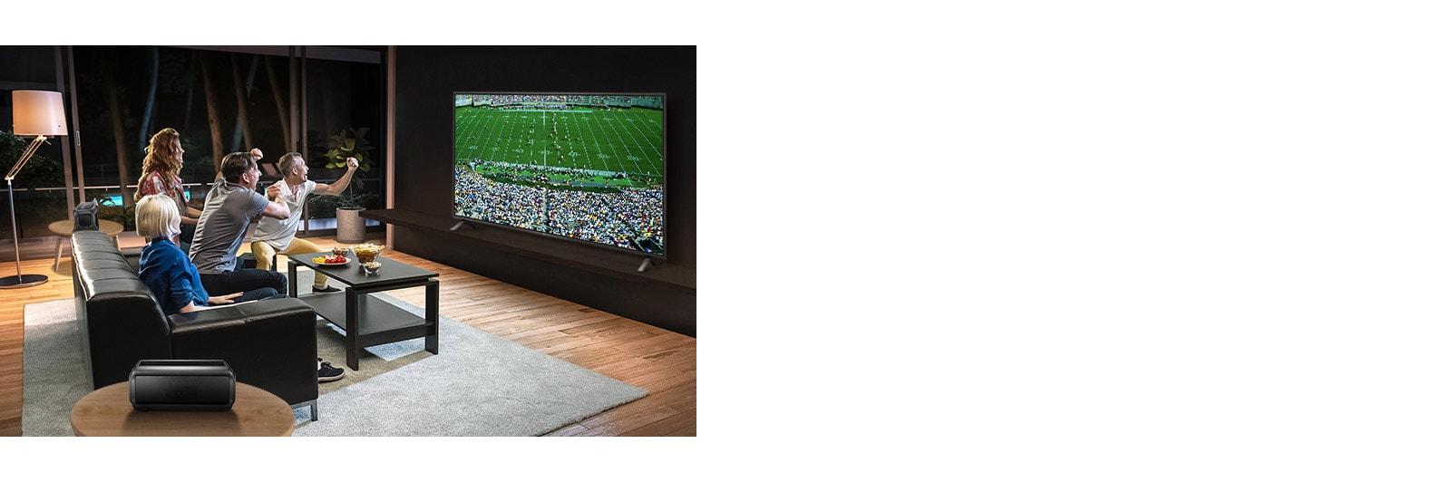 Persone che guardano una gara sportiva alla TV in soggiorno con altoparlanti Bluetooth posteriori.