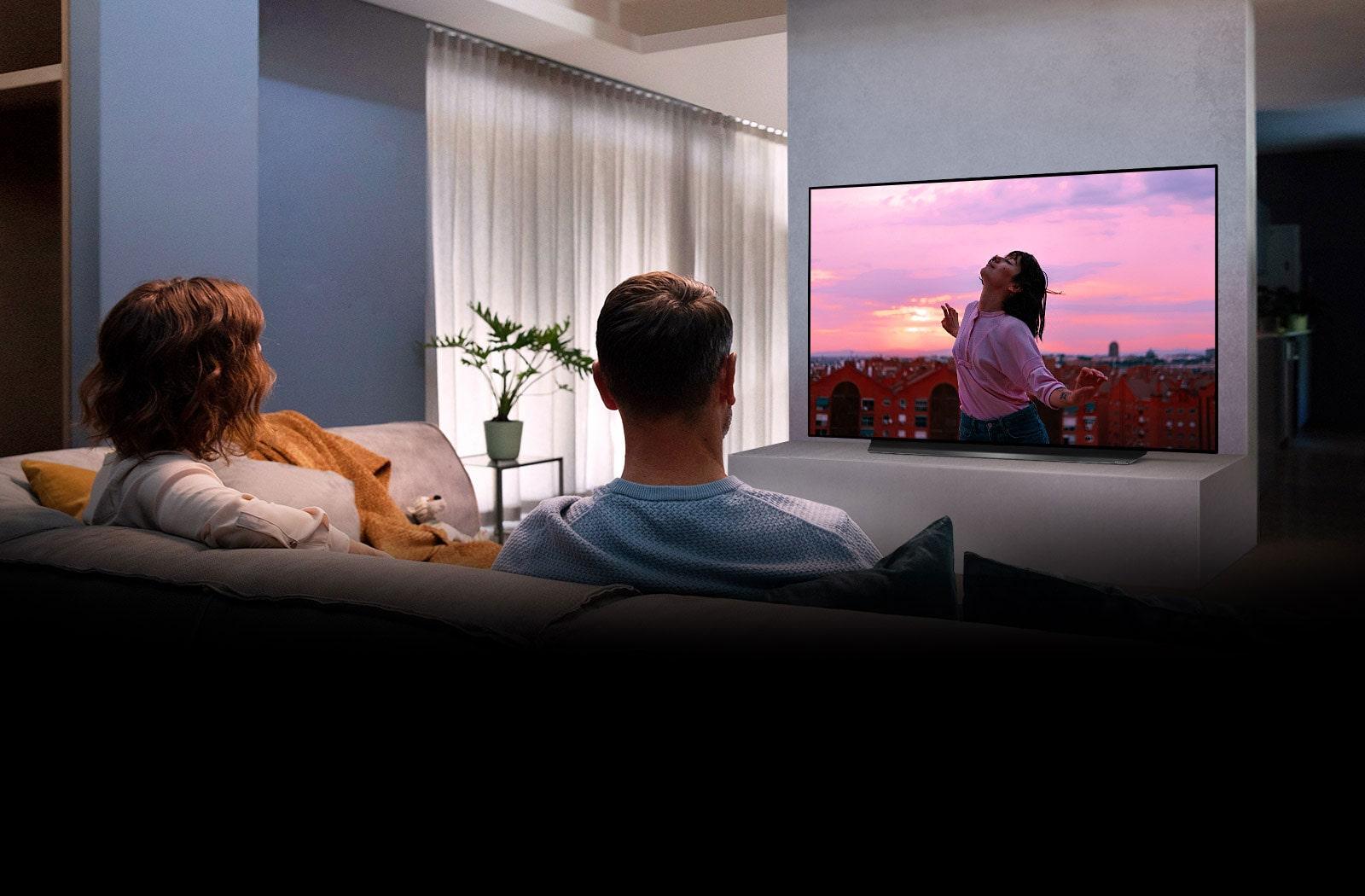 Una coppia seduta su un divano in soggiorno guarda un film romantico alla TV