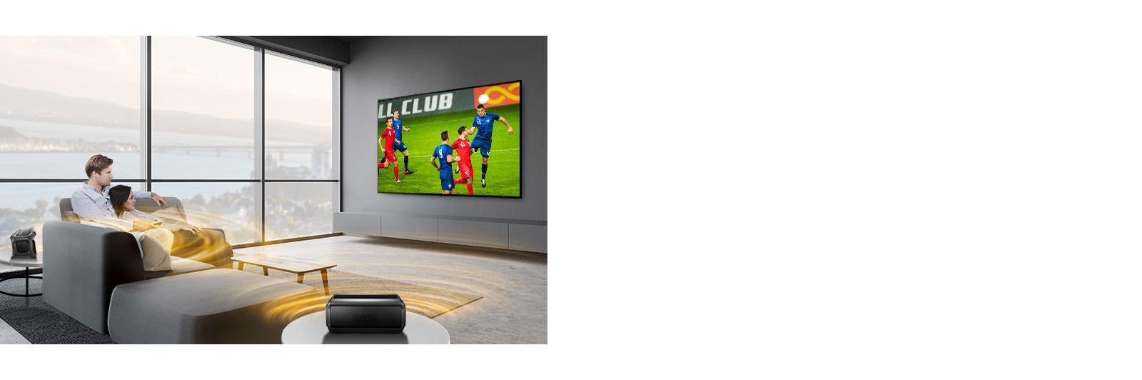 Мужчина и женщина смотрят спортивную игру в гостиной с помощью подключенных через Bluetooth тыловых колонок.