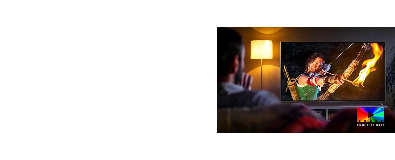 Мужчина сидит на диване, смотрит фильм в жанре экшн. Девушка на экране держит в руках натянутый лук и стрелу.