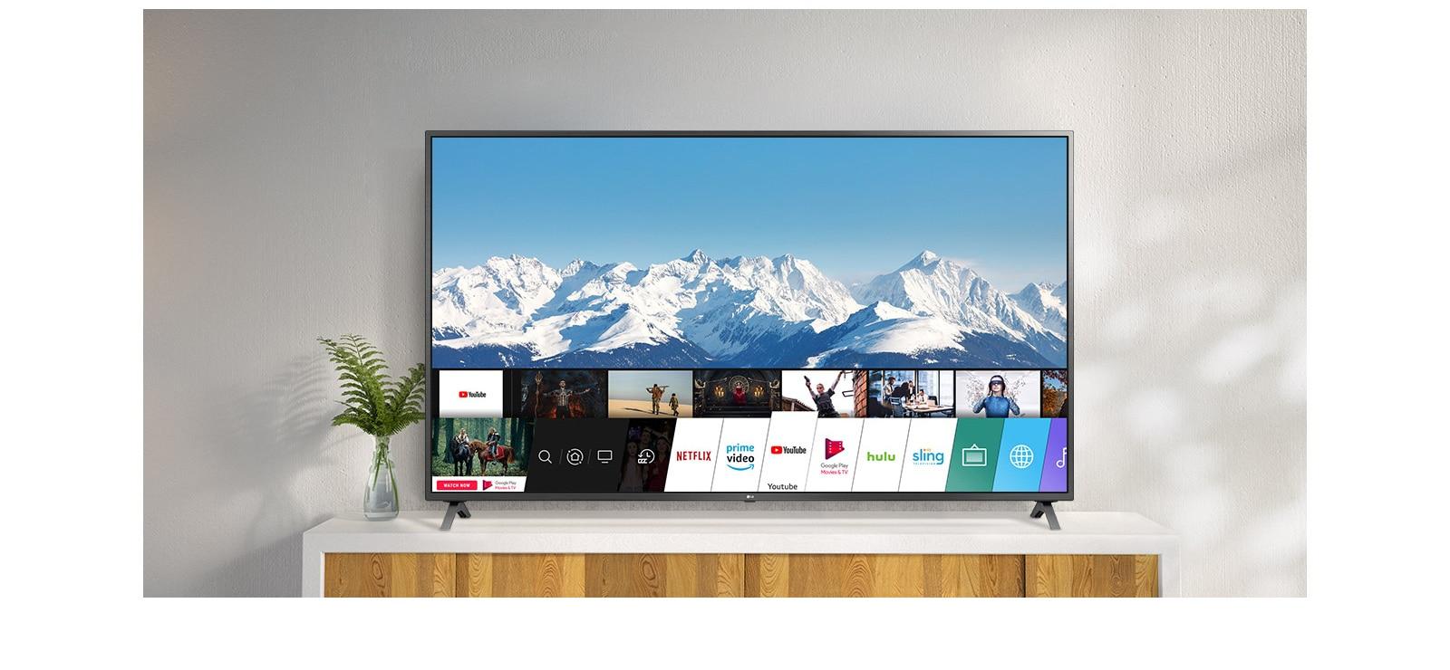 Телевизор стоит на белой тумбе на фоне белой стены. На экране показан рабочий стол с webOS.
