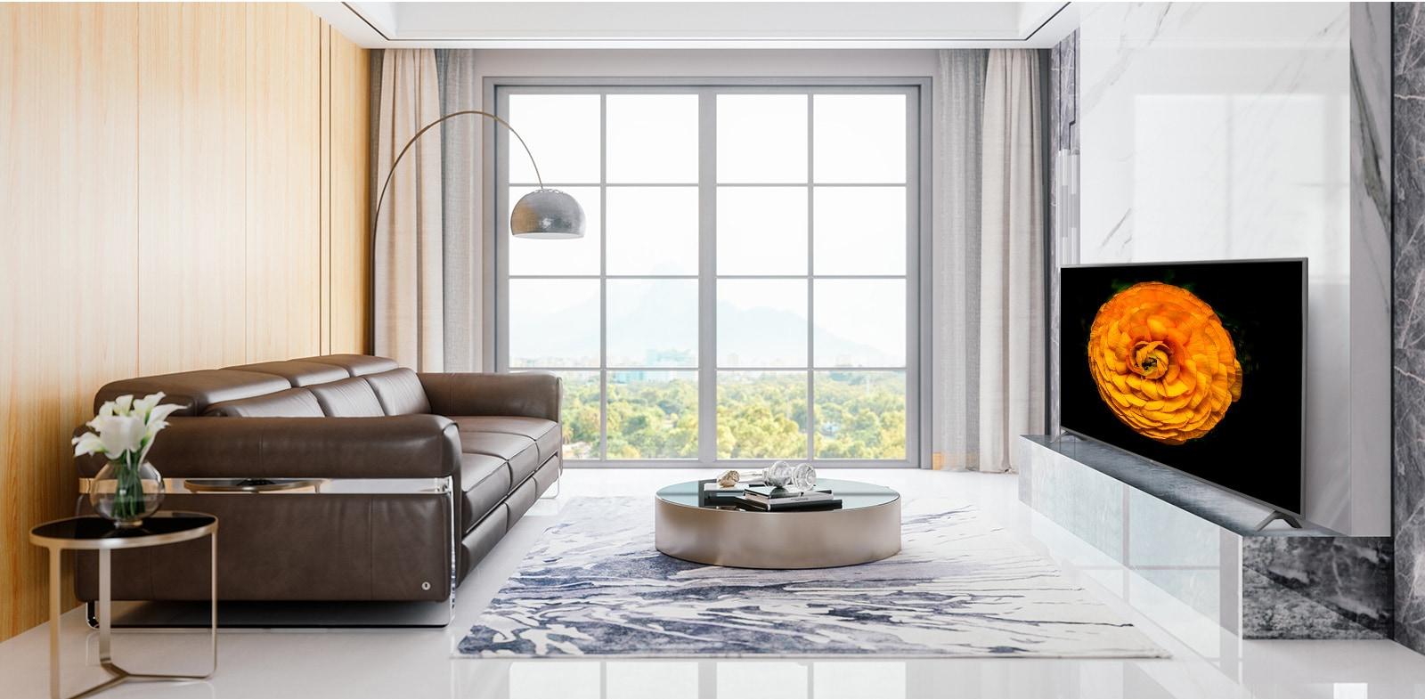 Телевизор LG UHD на стене в гостиной с минималистичным интерьером. На экране телевизора показано изображение цветка.