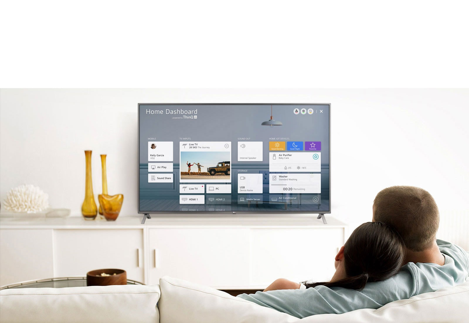 Un homme et une femme assis sur un canapé dans le salon avec le tableau de bord d'accueil sur l'écran du téléviseur.
