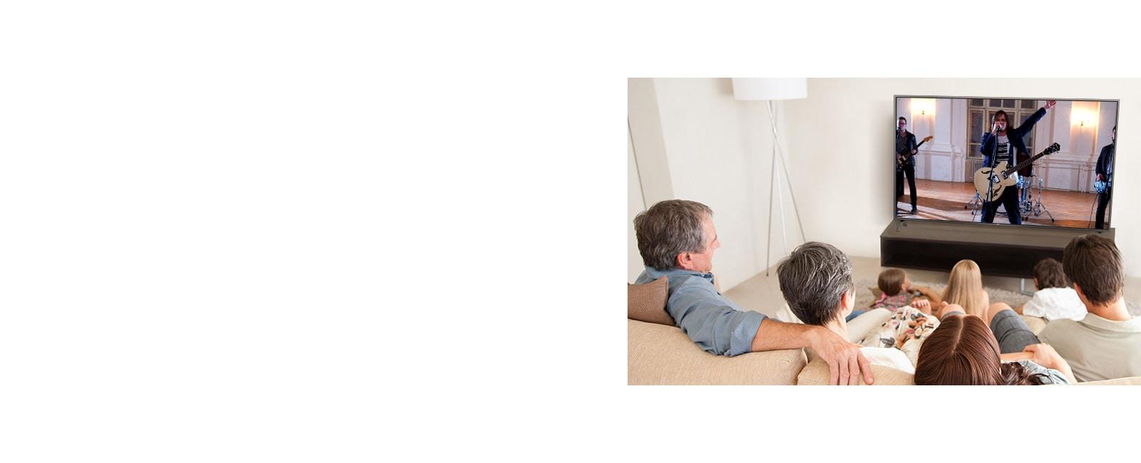 Une famille de sept personnes s'est réunie dans le salon, regardant un film. L'écran de télévision montre un groupe en train de jouer.