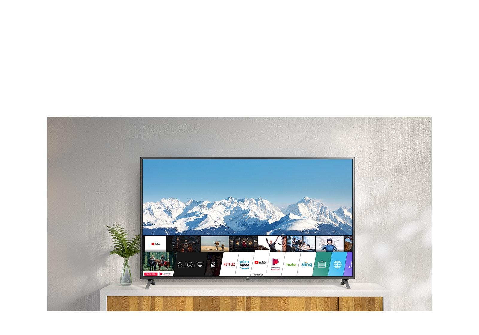 TV debout sur un support blanc contre un mur blanc. L'écran du téléviseur affiche l'écran d'accueil avec webOS.