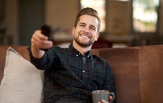 A man sitting on the sofa, holding a remote control with bright smile. The other hand is holding a mug.