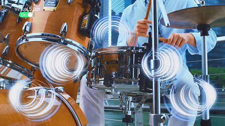 The man plays the drum and simulated sound effects emanate from the drum.