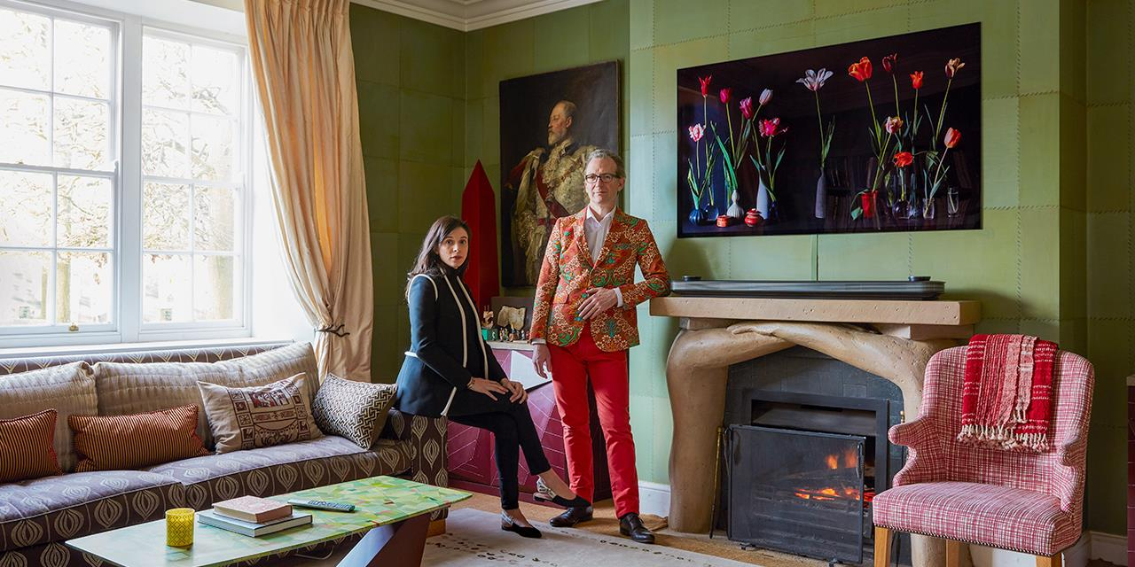 Ashley Hicks and his wife in their living room of their Oxfordshire home, with fireplace, antique chairs and numerous pieces of art