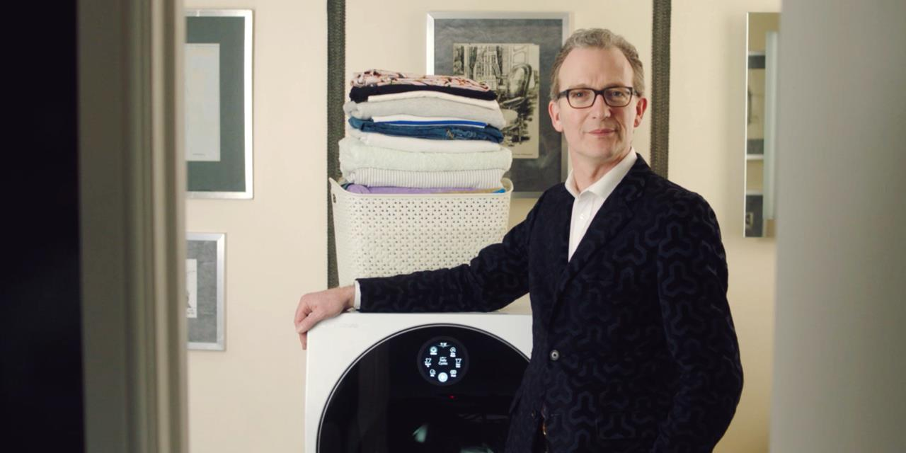 Ashley Hicks with his hand on the LG SIGNATURE TWINWash washing machine with a pile of laundry in the background