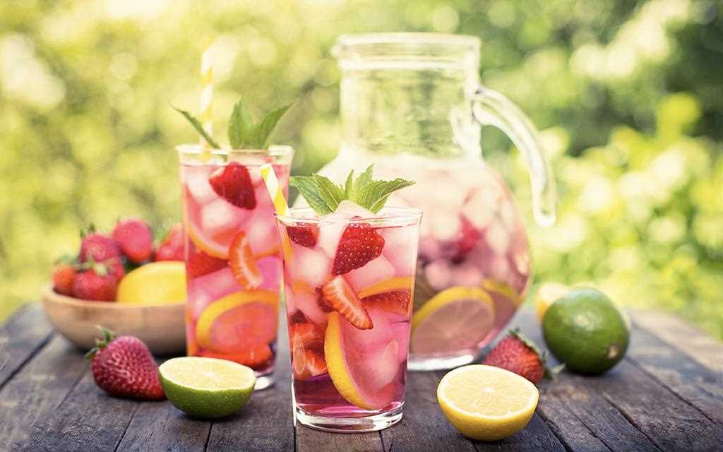 A front view of fruity summer punches with strawberry, limes, and lemons.