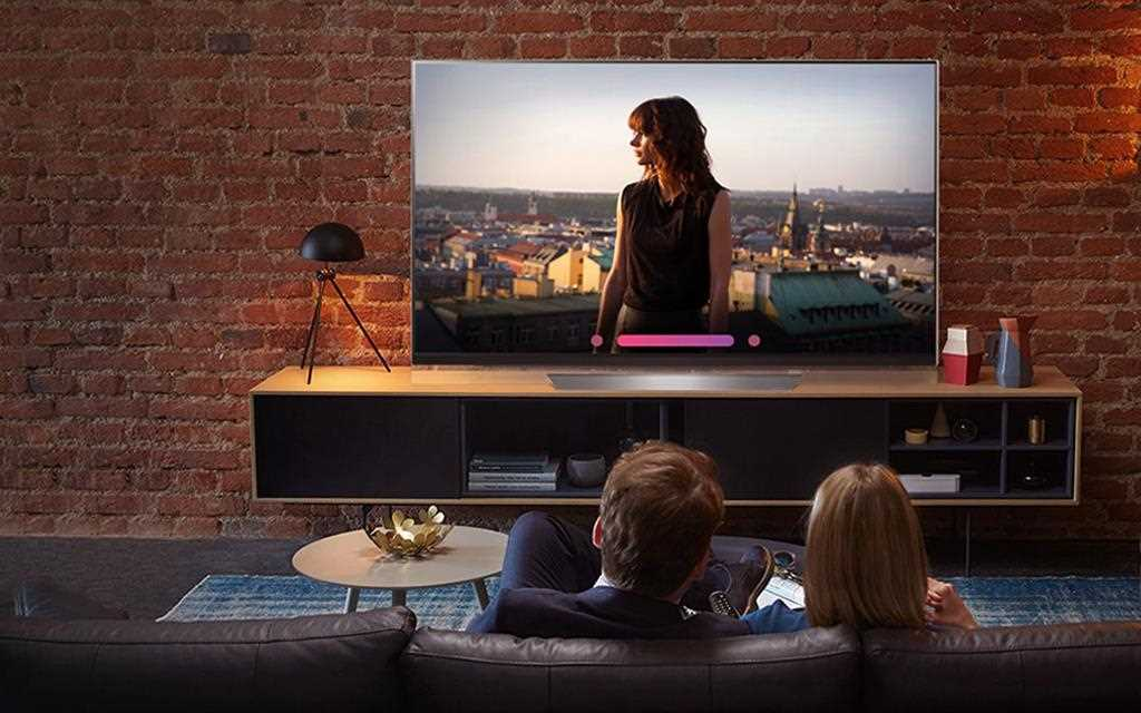An image shows a couple watching lg super uhd tv and testing the voice command from its artificial intelligent feature.