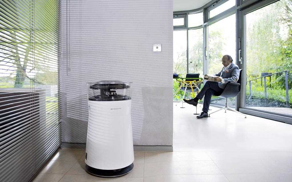 LG SIGNATURE air purifier in a hallway while a man works in his office with a view of the garden