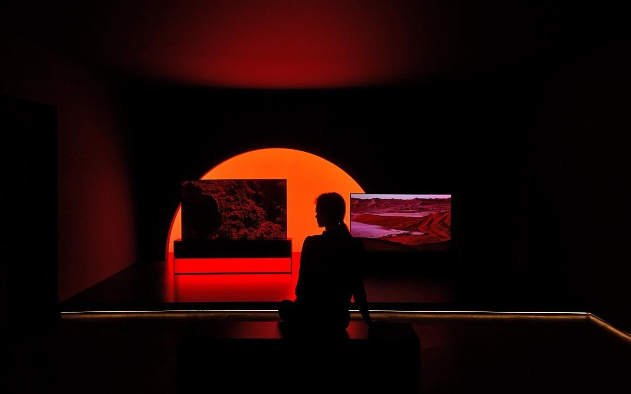 A woman sits in front of the LG SIGNATURE Rollable TV, on show at Milan Design Week | More at LG MAGAZINE