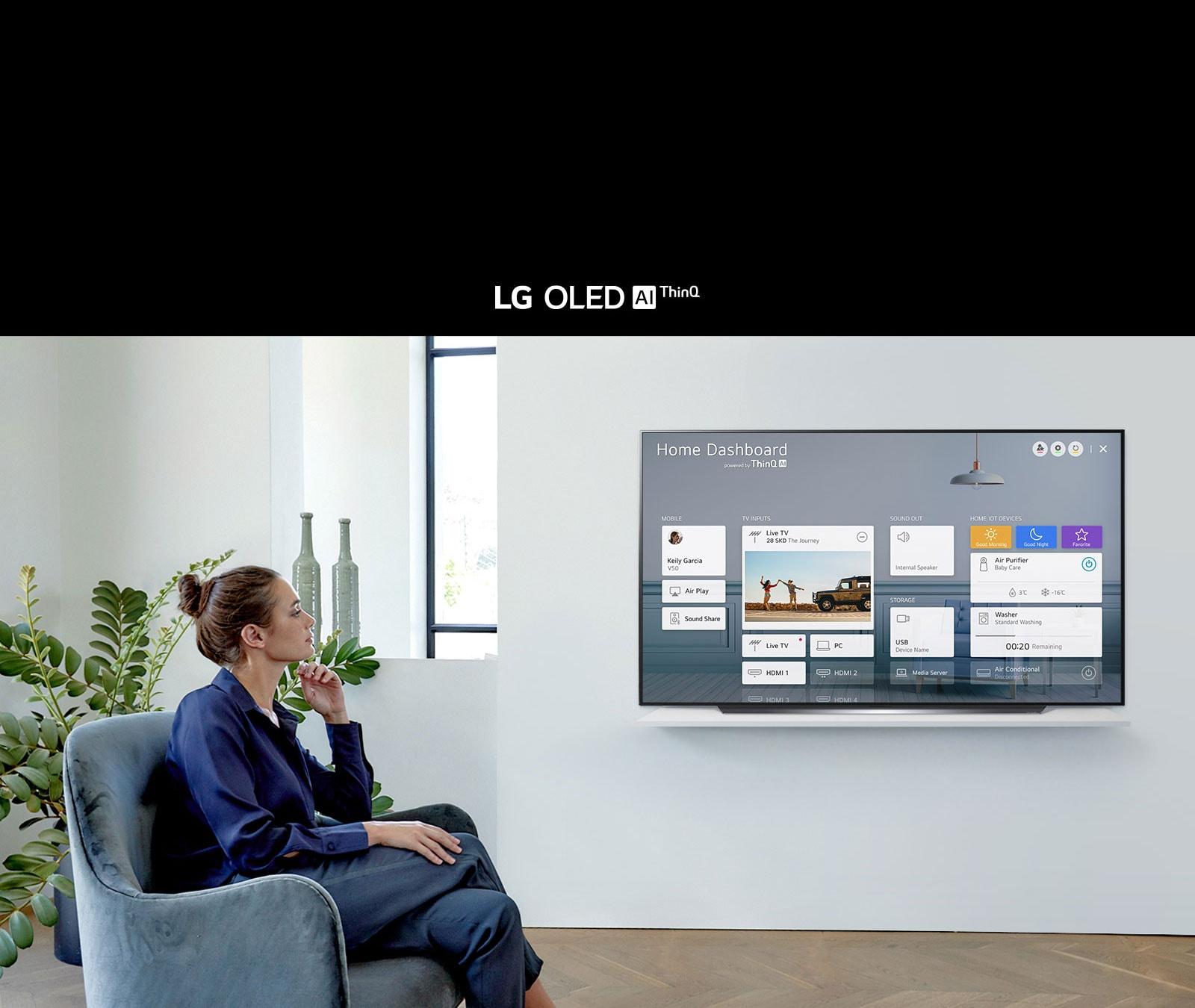 Femme assise sur une chaise dans le salon avec le tableau de bord sur l'écran du téléviseur