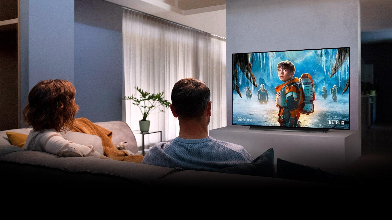Couple assis sur un canapé dans le salon en regardant un film romantique à la télé