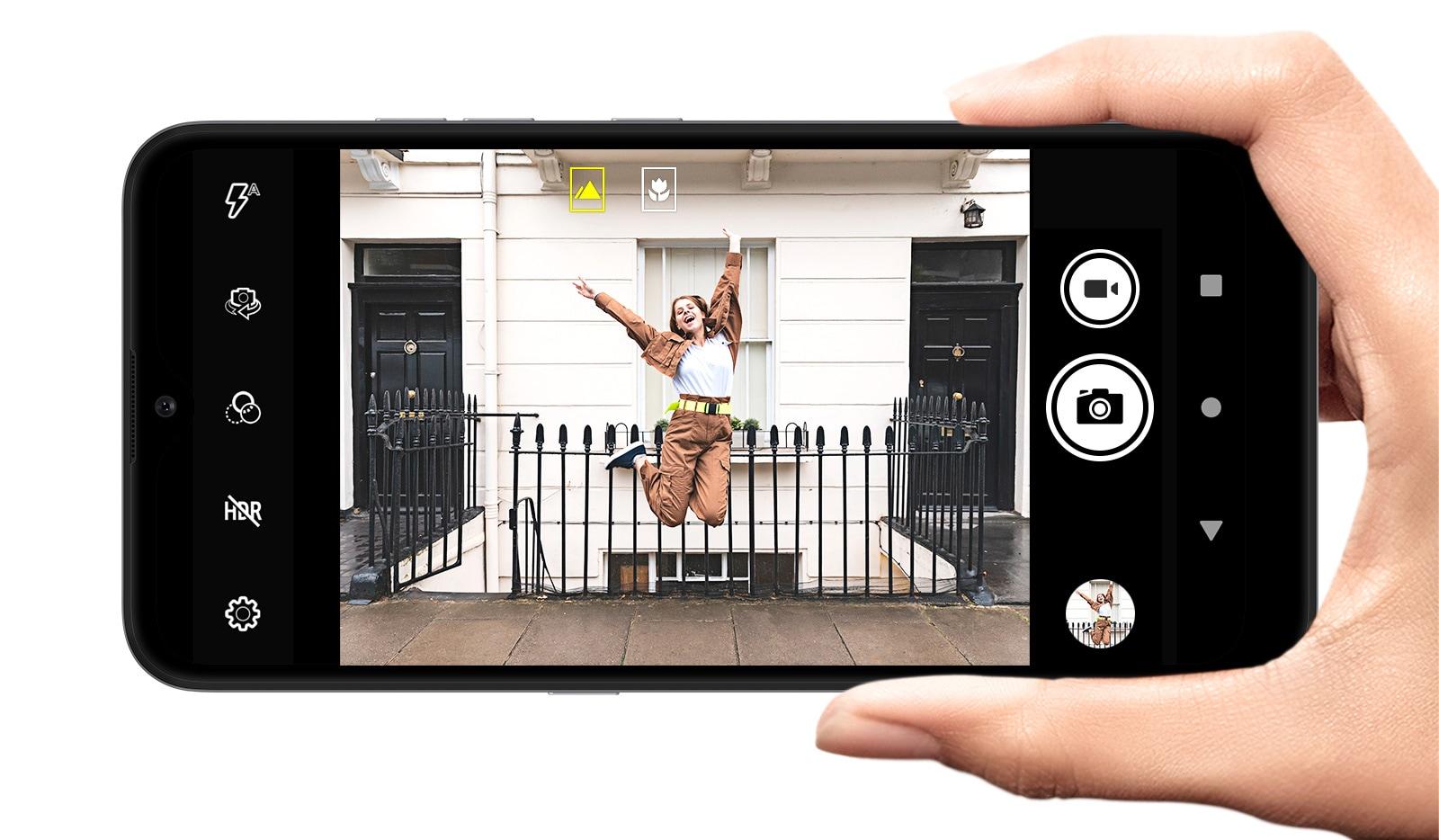 Smartphone disparando a una mujer posando para un salto en la calle