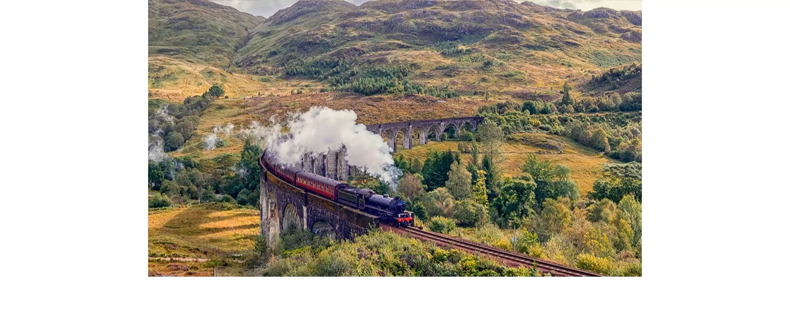 A train giving off steam on the rail is in the middle of the mountain with the text of 'Quad Core Processor 4K' on the bottom left.