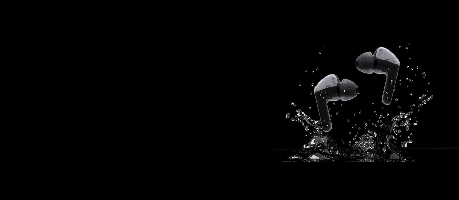 An image of two black earbuds jumping on a puddle of water
