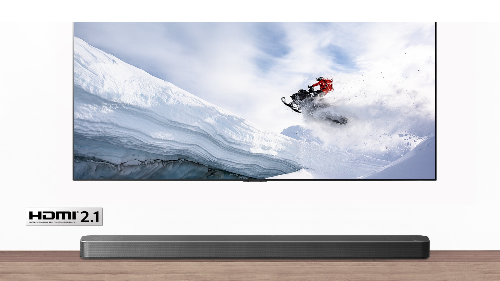 TV and Soundbar are seen from the front. TV shows man riding snowmobile in the snowy mountains. HDMI 2.1 logo is below TV.
