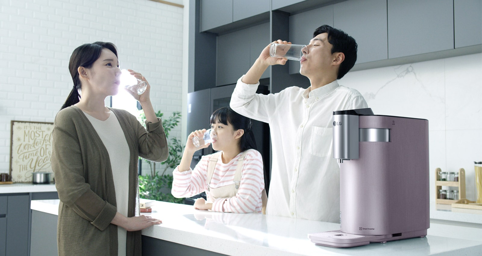 A family of three stand around a kitchen counter drinking water with the PuriCare Water Purifier on the counter in the foreground.